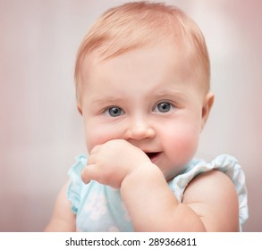 Closeup portrait of a beautiful little baby girl with hand in the mouth over pastel pink background, carefree childhood, precious innocent kid