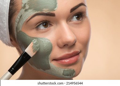 Close-up Portrait of beautiful looking aside girl in spa with a  towel on her head applying facial clay mask and beauty treatments with brush on her face isolated on beige background