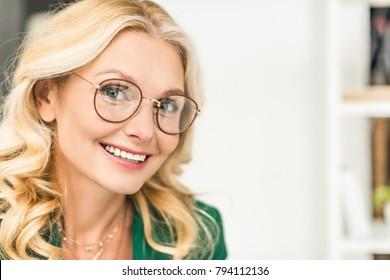 close-up portrait of beautiful mature businesswoman in eyeglasses smiling at camera