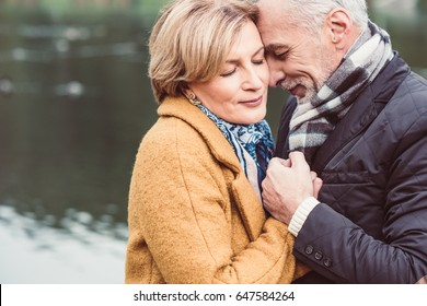 Close-up portrait of beautiful mature couple standing and holding hands near lake in autumn park