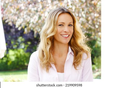 Close-up portrait of beautiful mature woman sitting at garden.