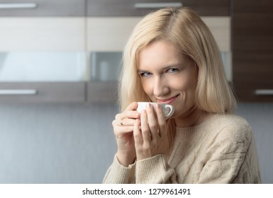 Close-up portrait of a beautiful mid age woman with cup of coffee. Attractive and happy blonde in sweater drinks coffee. Copy space.