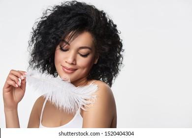 Closeup portrait of beautiful mixed race woman touching her skin with white ostrich feather enjoying its softness, studio shot