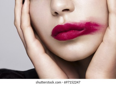 Close-up portrait of a beautiful model with deep red color lipstick on her lips.