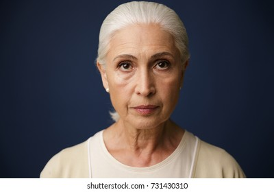 Close-up portrait of beautiful old woman, over dark blue background