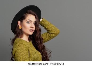 Nahaufnahme eines schönen und positiven jungen Mädchens auf schwarzem Hut einzeln auf grauem Hintergrund