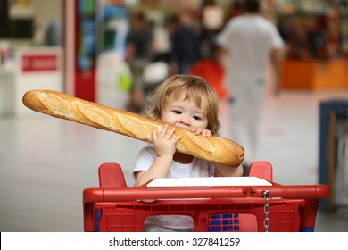 Closeup portrait of beautiful pretty cute hazel-eyed kid with shoulder-length blond wavy hair holding and biting French bread riding red and blue shopping trolley against grey background, horizontal