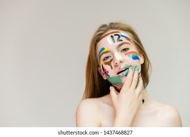 A close-up portrait of a beautiful pretty red-haired woman girl on a white background in the studio with pictures on her face. Smiles, shows emotions.