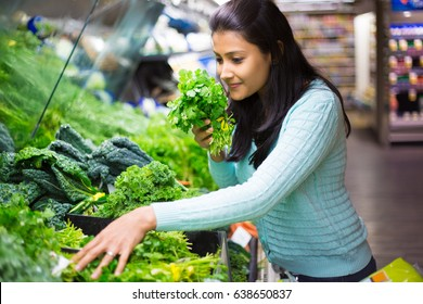 Closeup portrait, beautiful, pretty young woman in sweater picking up, smelling, choosing green leafy vegetables in grocery store