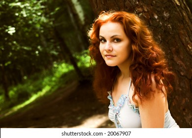 Close-up portrait of a beautiful red-headed girl in forest