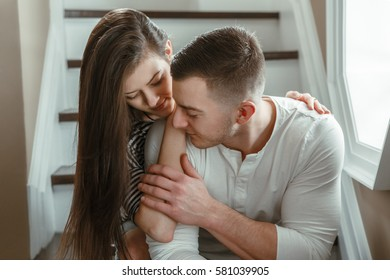 Closeup portrait of beautiful romantic young couple man woman in love hugging, kissing, indoors at home, toned with filters, sitting on stairs indoor