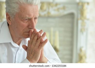 Close-up portrait of beautiful sad senior man at home