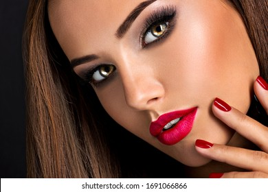 Closeup portrait of beautiful seductive woman with dark brown eye makeup and bright red lips and nails