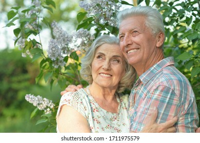 Close-up portrait of beautiful senior couple posing in the summer park