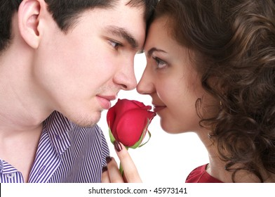 Closeup portrait of beautiful sexual couple with red rose isolated over white background