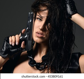 Closeup portrait of beautiful sexy brunette woman with revolver gun and wet hair on dark background