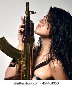 Closeup portrait of beautiful sexy brunette woman with fashion gold automatic rifle gun on gray background