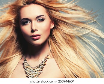 Closeup portrait of the beautiful sexy woman with long blonde hair. Fashion model posing in the studio on a black background with flying hair.
