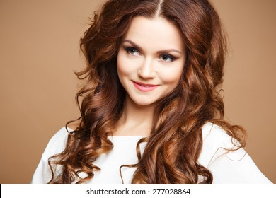 Close-up portrait of beautiful sexy young woman with long brown hair over brown background