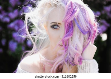 close-up portrait of a beautiful sexy young blonde girl hipster with lilac and pink hair on the background of blooming lilacs, posing