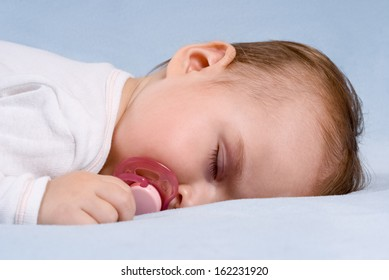 Close-up portrait of a beautiful sleeping baby on blue blanket. Use the photo to represent life, parenting or childhood.