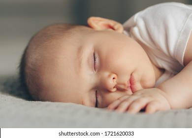 Close-up portrait of a beautiful sleeping baby boy on grey