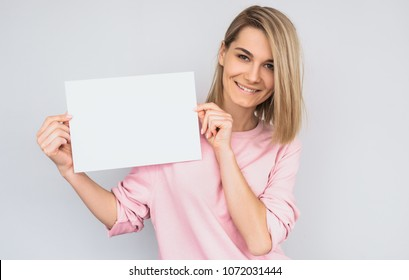 Closeup portrait of beautiful smiling blonde female wearing pink sweater, posing with white blank paper with copy space for your advertisement information and looking at camera, against white wall.