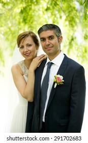 Closeup portrait of beautiful smiling bride and groom standing under big tree