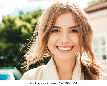 Closeup portrait of beautiful smiling brunette model. Trendy female posing in the street background at sunset. Funny and positive woman having fun outdoors
