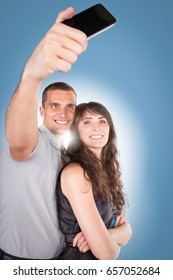 Close-up portrait of beautiful smiling couple hugging and looking at smartphone. On white background. Cellphone concept.
