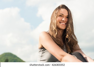 Close-up portrait of beautiful smiling female relaxing in the nature on warm sunny day with copyspace