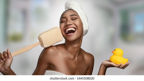 Close-up portrait of a beautiful smiling happy woman holding body scrubber and yellow rubber duck isolated on bright background. Beauty treatments and cosmetics spa therapy
