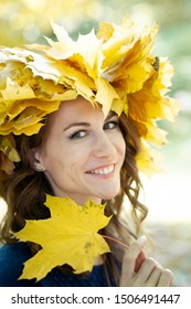Close-up portrait of beautiful smiling happy young brunette woman with wreath of yellow maple leaves on her head and in blue jersey. girl holds autumn maple leaves in hand. Golden park in background.