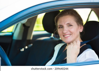 Closeup portrait beautiful, smiling, happy, attractive woman pulling on seatbelt inside white car. Driving safety, buckle up to prevent traffic death accidents concept. Save life. Face expression