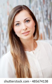 Closeup portrait of beautiful smiling nice young white Caucasian business woman with blue eyes long blond hair wearing white office blouse shirt, looking in camera, slavic Russian face