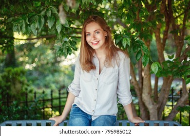 Closeup portrait of beautiful smiling white Caucasian girl woman with long blonde hair and blue eyes wearing white shirt and jeans outside in summer park in green foliage trees looking in camera.