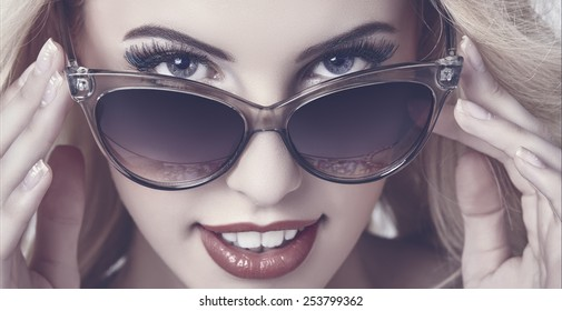Closeup portrait of a beautiful smiling woman giving a seductive hypnotic look over dark sunglasses. Mate tinted color grading.