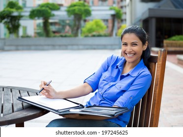 Closeup portrait, beautiful, smiling young business woman in blue shirt, sitting, taking notes outside, isolated trees background