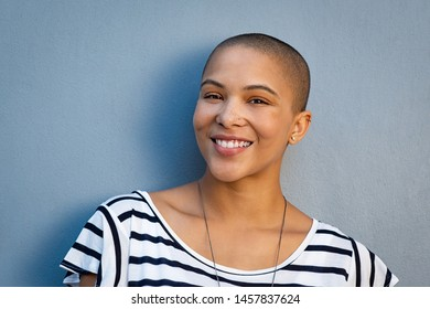 Closeup portrait of beautiful stylish woman on lightblue background. Smiling bald girl looking at camera with copy space. Cheerful and satisfied young woman with shaved head.