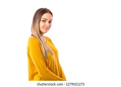 Closeup portrait of a beautiful teenage girl wearing yellow sweater posing over white background