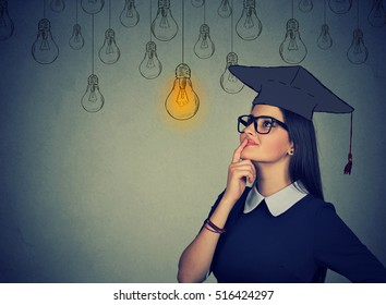 Closeup portrait beautiful thoughtful graduate student girl young woman in cap gown looking up at bright light bulb thinking isolated gray wall background. Graduation ceremony future career concept