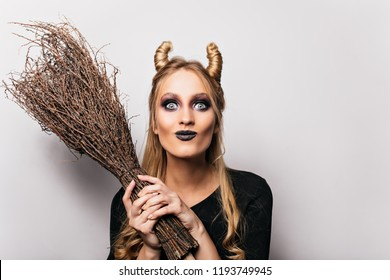 Close-up portrait of beautiful witch with gray eyes. Romantic young wizard holding her broom on white background.