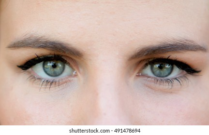 Close-up portrait of a beautiful woman with blue eyes, looking at camera