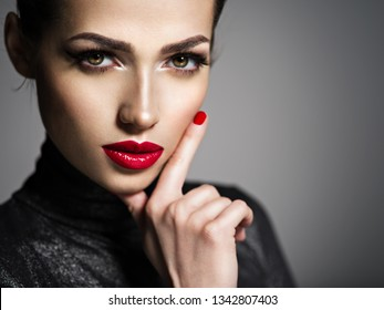 Closeup portrait of beautiful woman with bright make-up and red nails. Sexy young adult girl with red lipstick.
