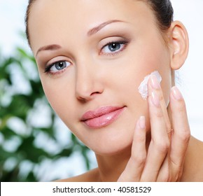 Close-up portrait of beautiful woman caring of her face