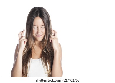Close-up portrait of a beautiful woman closing her eyes, crossing her fingers hoping for the best, isolated on white background