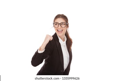 Closeup portrait of a beautiful woman euphoric pumping fist in jubilation, excited girl looking back to side wearing business wear, formal black suit, shirt cutout isolated on a pure white background