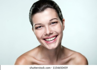Close-up portrait of a beautiful woman with an expression of emotions on a light background