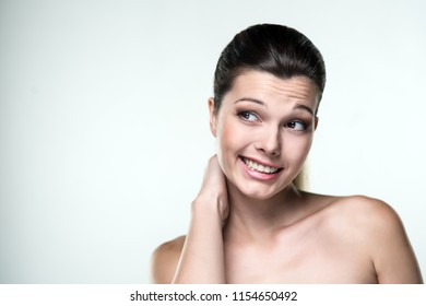 Close-up portrait of a beautiful woman with an expression of emotions looks sideways to the left on a light background