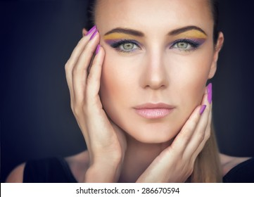 Closeup portrait of a beautiful woman face over dark background, gorgeous model with colorful stylish makeup, fashion look, luxury beauty salon